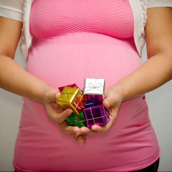 Pregnant woman with little gift box